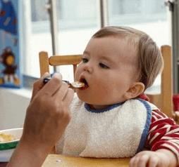 よだれかけをして離乳食を食べる金髪の外国人の赤ちゃん