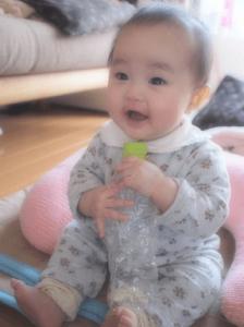 座ってペットボトルをつぶしながら笑っている生後6ヶ月の赤ちゃん