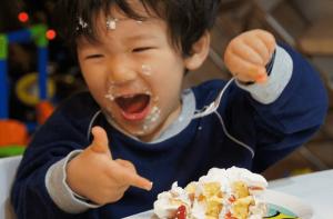 クリスマスケーキに大喜びで顔にケーキを付けている子供